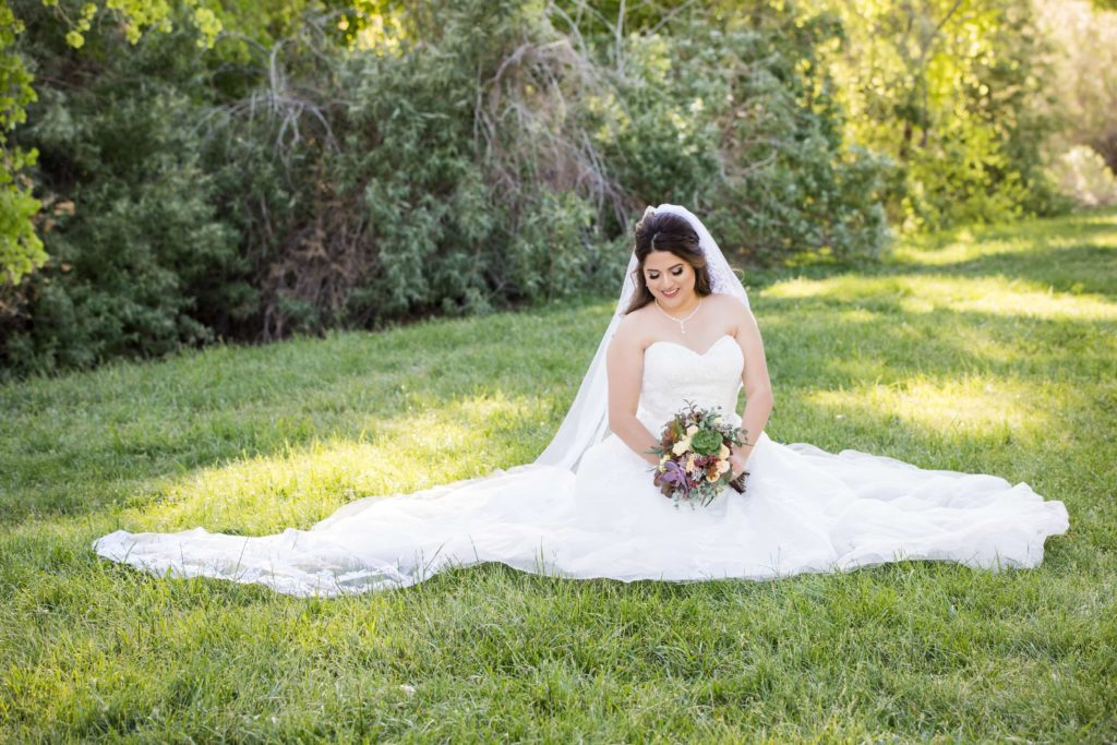 Bride in wedding dress with flowers poses on green lush lawn of park.