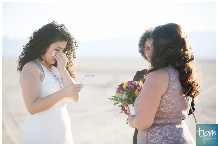 A bride crying as she reads her vows to her bride during their ceremony.