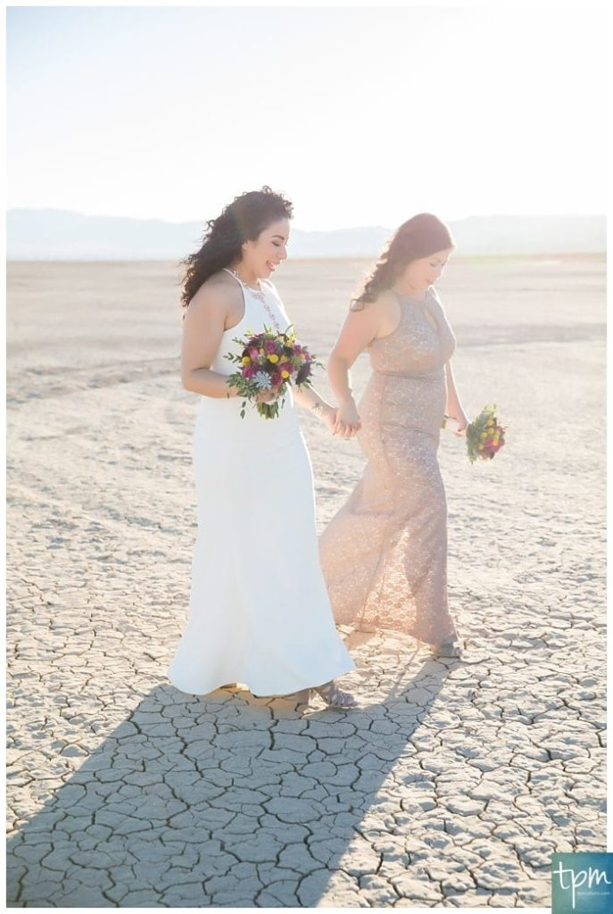 Two brides walk side by side holding hands at sunset.