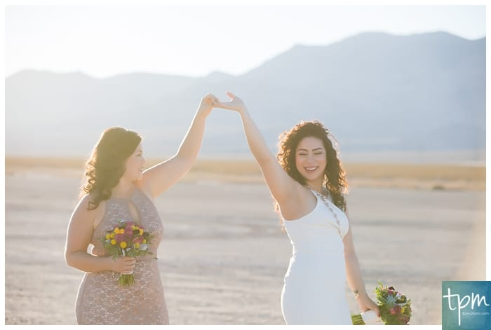 Two brides celebrating their wedding at a desert dry lake bed.