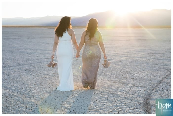Two brides walking in to the sunset holding hands.