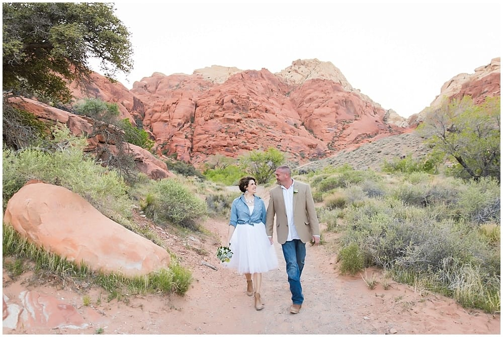 Newlyweds walking along a dirt path in the scenic Las Vegas desert.