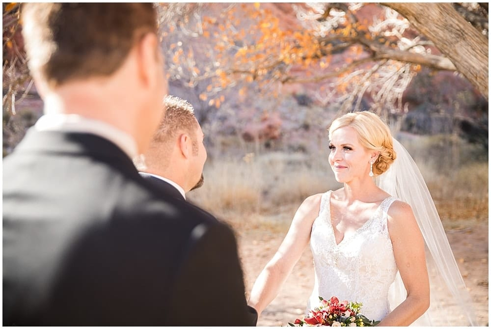 Bride looking with affection at her groom during a ceremony under a fall colored tree in Las Vegas.
