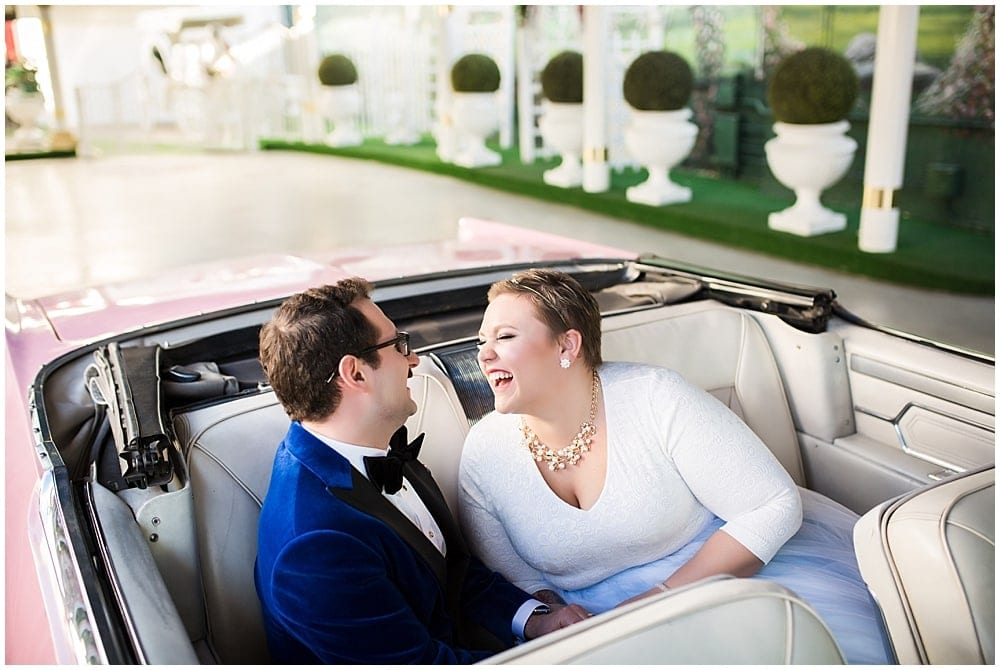 Bride and groom laughing, sitting in a pink cadillac in Las Vegas.