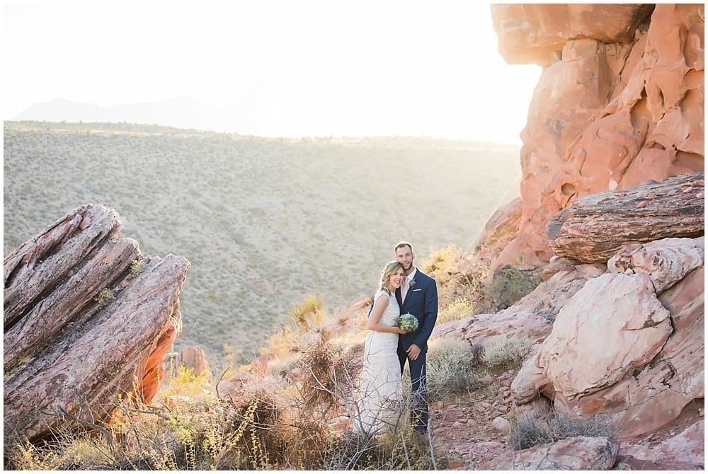 Bride and groom standing next to each other on a mountain cliff at sunset.