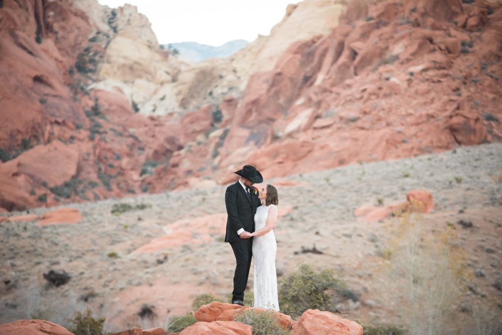 Bride and Groom with cowboy hat in Red Rock Canyon.