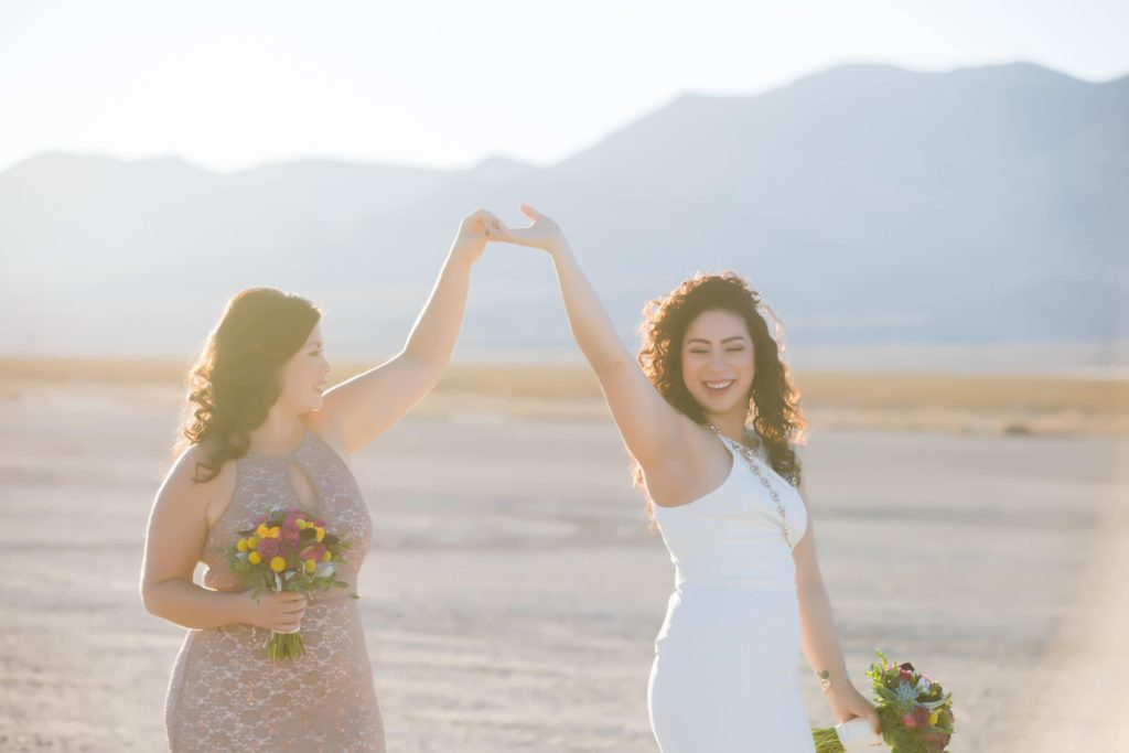 Two brides hold hands in the air in the Las Vegas desert.