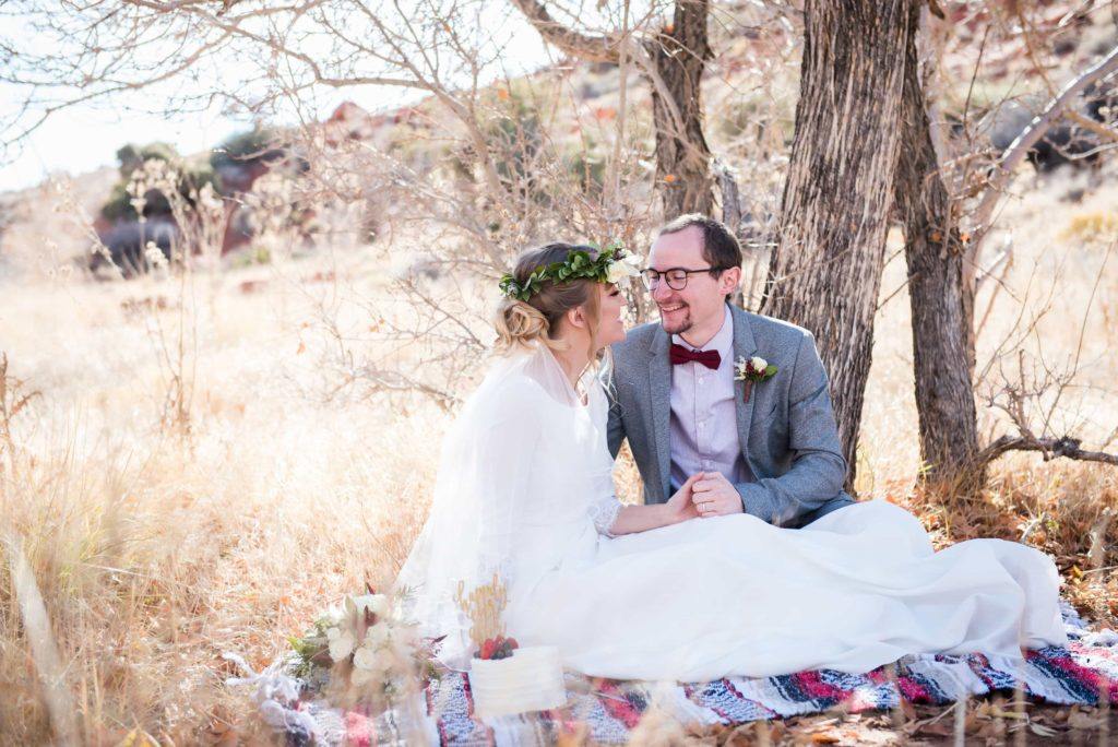 Bride and Groom sit on a plaid cozy blanket during a fall wedding photo shoot.