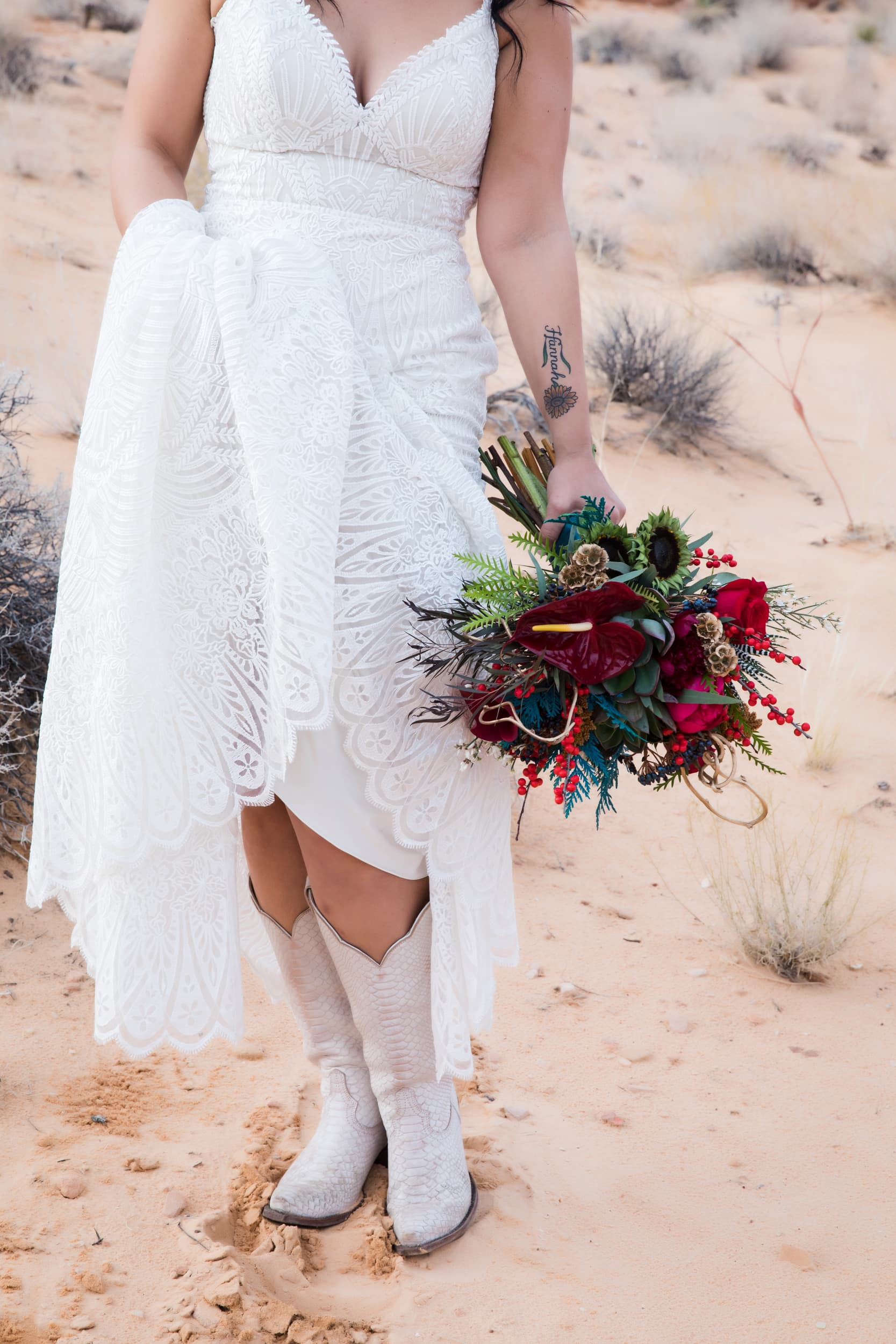 Bride in wedding cowboy boots holding gorgeous red bouquet.