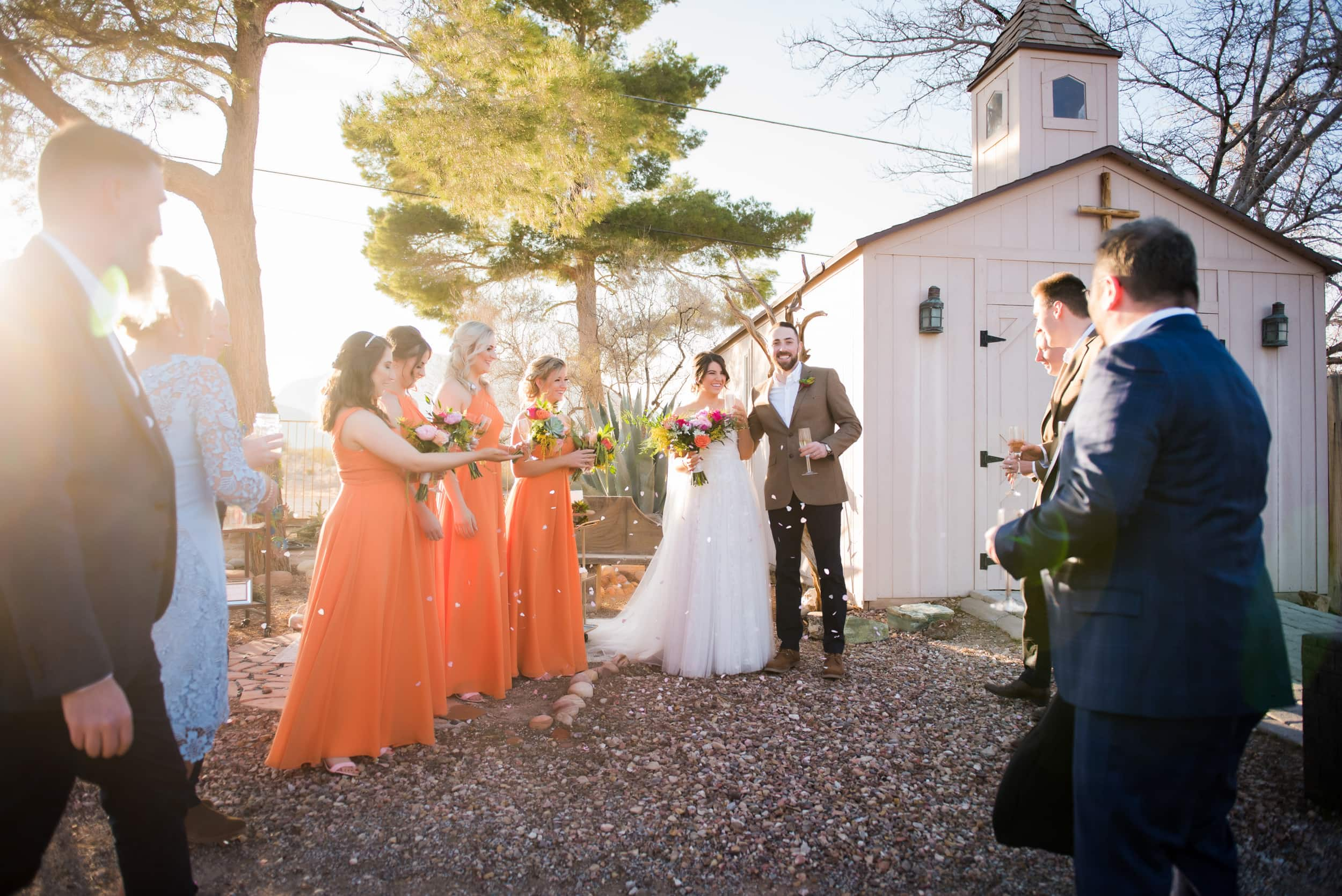 Bridal party in bright orange bridemaid dresses.