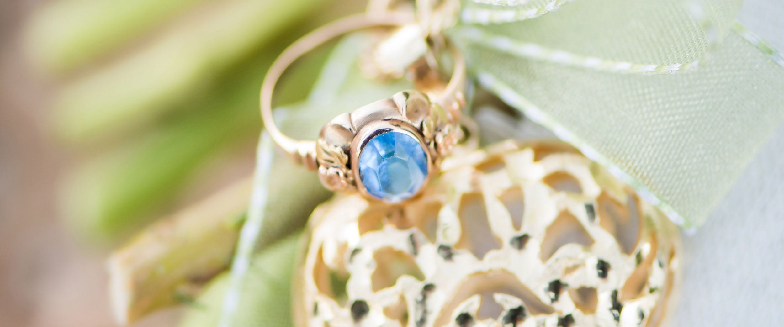 A photo of a blue gem in a gold ring setting.