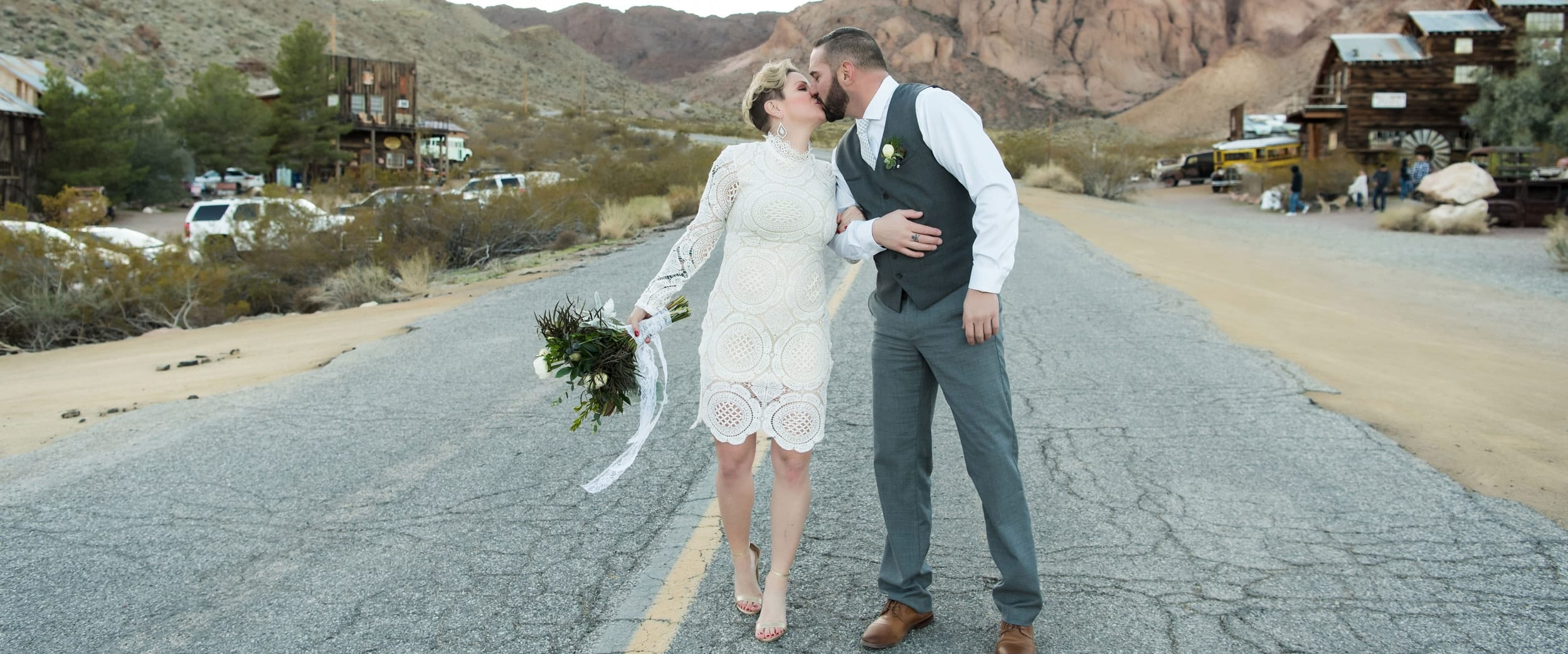 Bride and groom kissing in the middle of a deserted road.