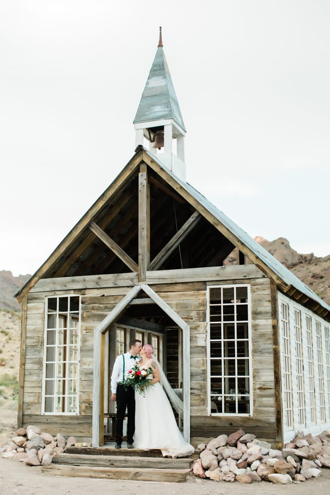 Hayley and Andrew kiss in front of the Eldorado Canyon Chapel.
