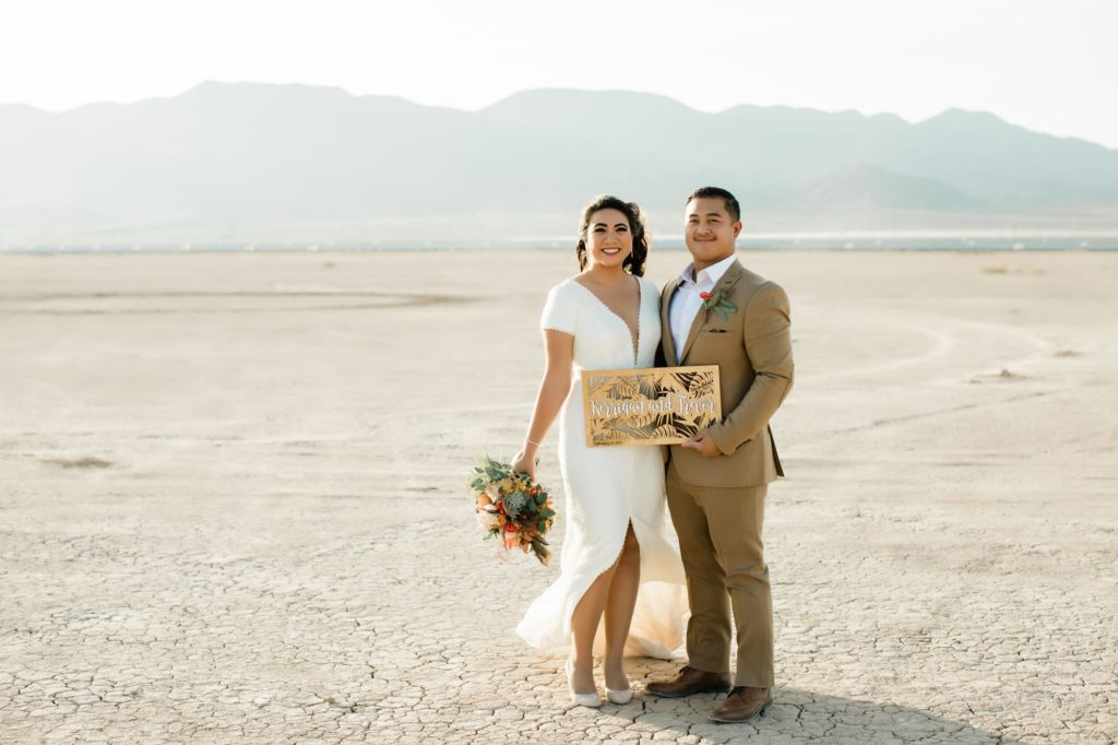 Kerrigan and Trevor at the Dry Lake Bed with wooden sign.