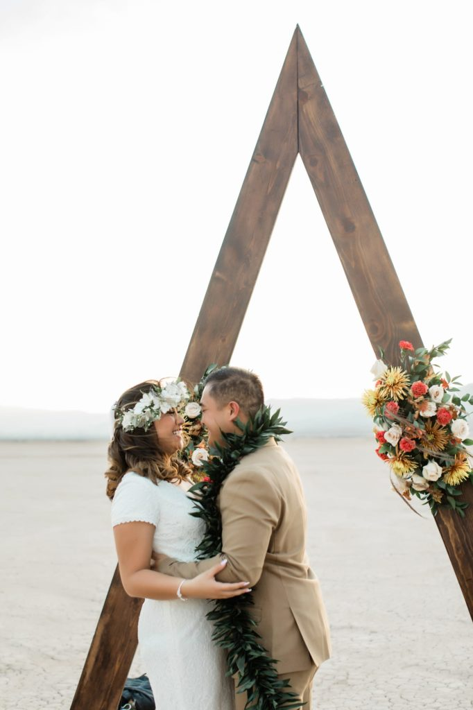 Kerrigan and Trevor kissing in front of their ceremony arbor.