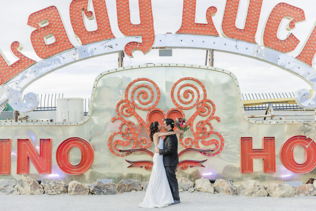 Newlywed couple standing in front of Lady Luck sign at the Neon Museum.