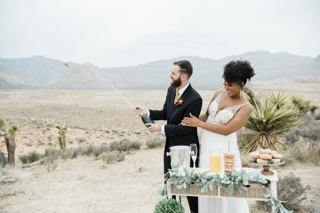 Smiling bride and groom, opening a bottle of champagne in the desert.
