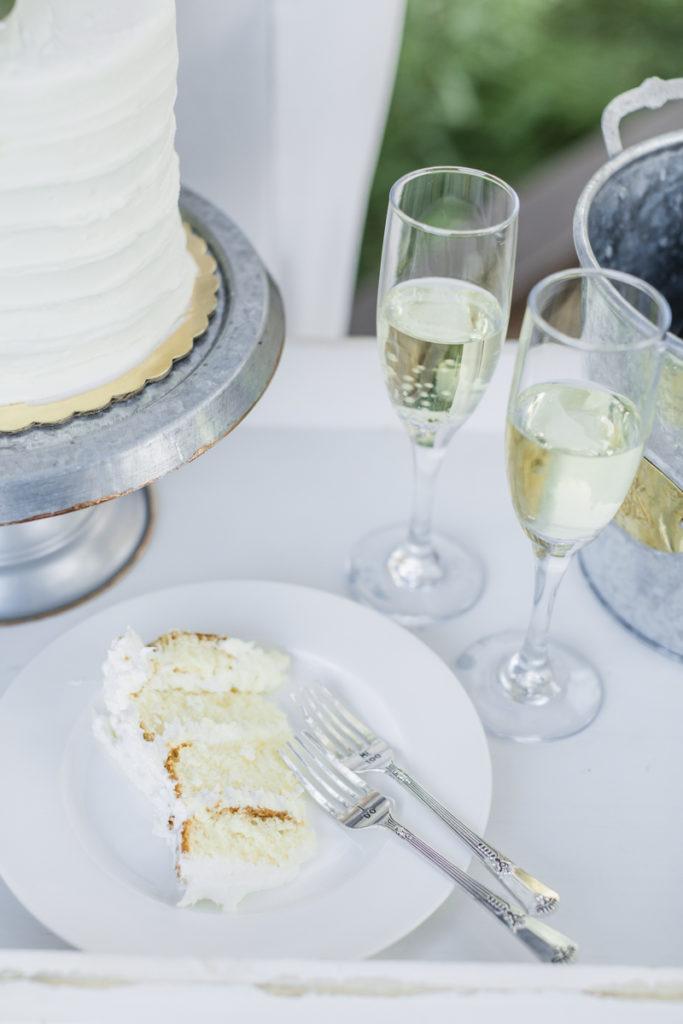 White wedding cake next to champagne glasses.