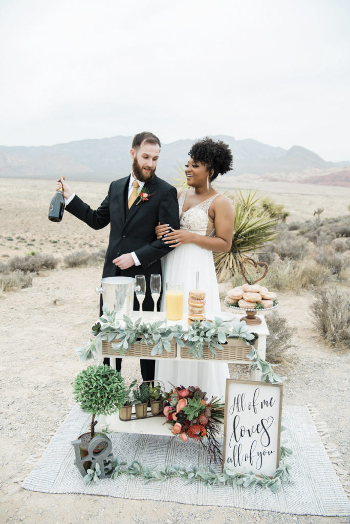 Newlywed couple opening champagne at mini reception.