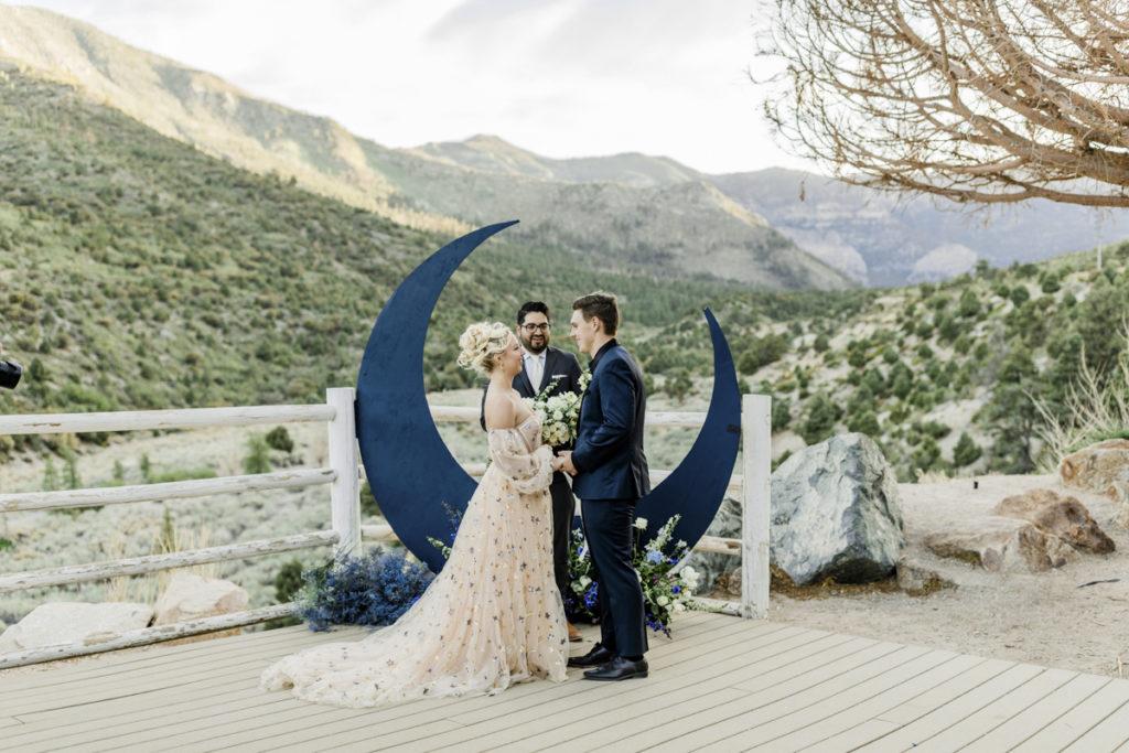 Wedding ceremony in front of moon art.