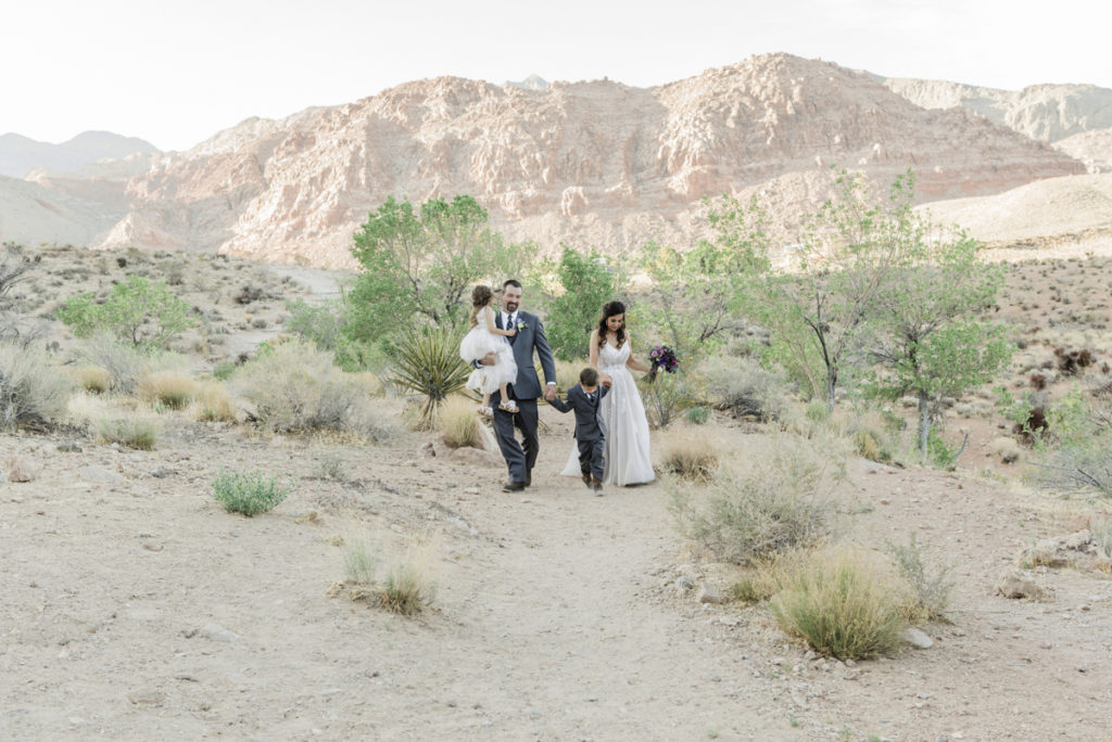 Bride and groom walking with their children after a wedding ceremony.
