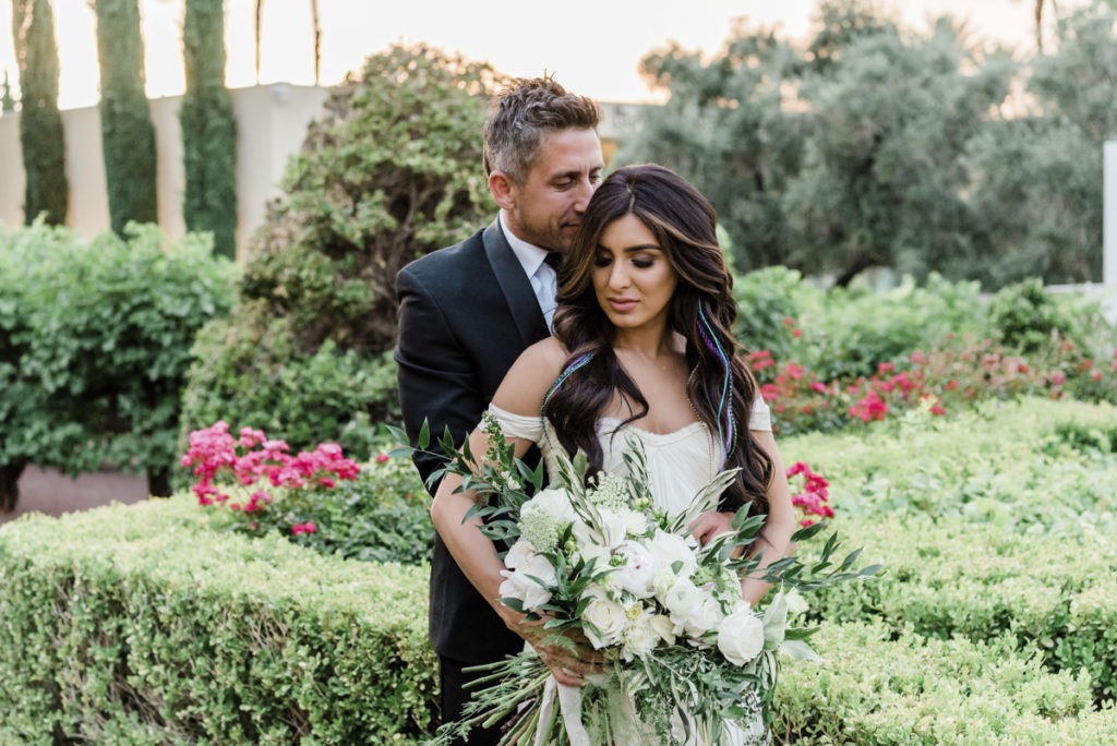 Newlywed couple embrace in a garden of flowers.