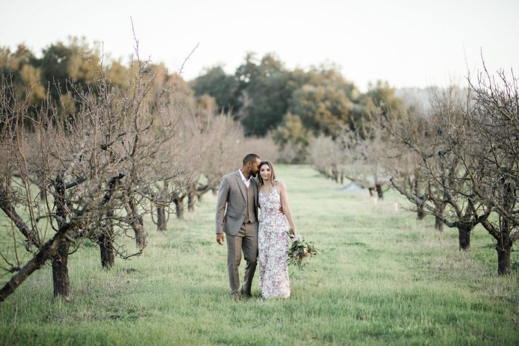 Newlywed couple walking in vineyard.