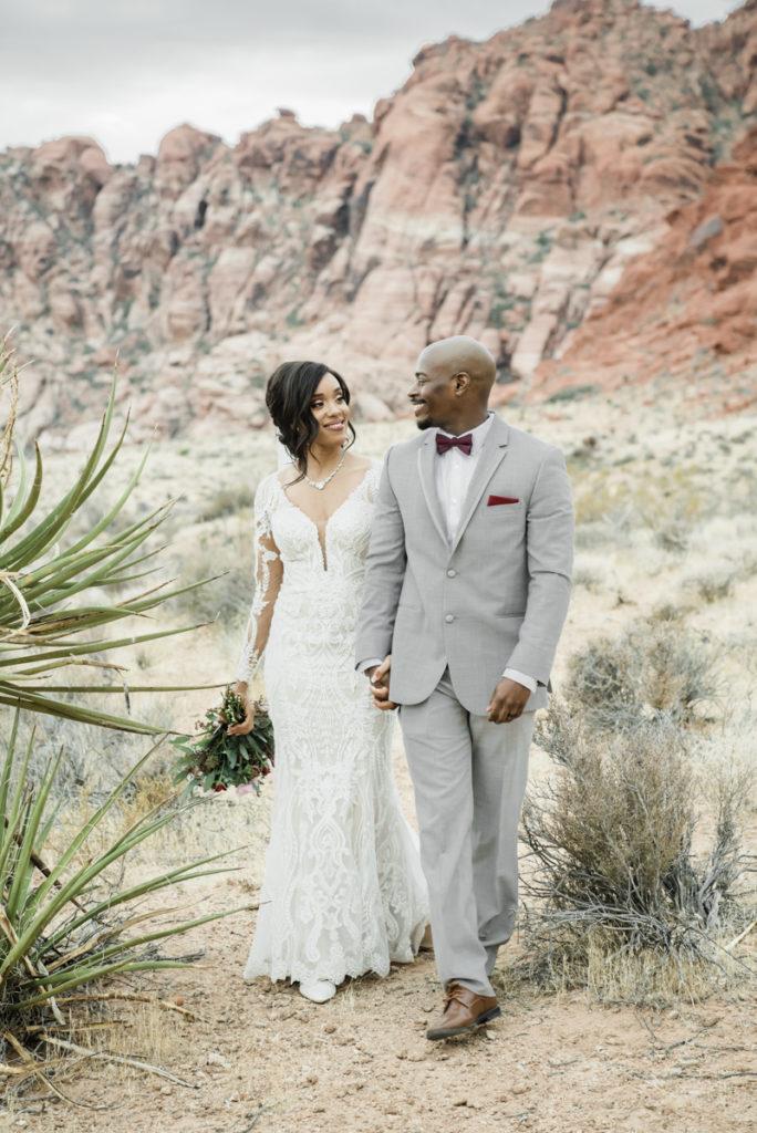 Shala & Michael walk hand in hand in the desert.