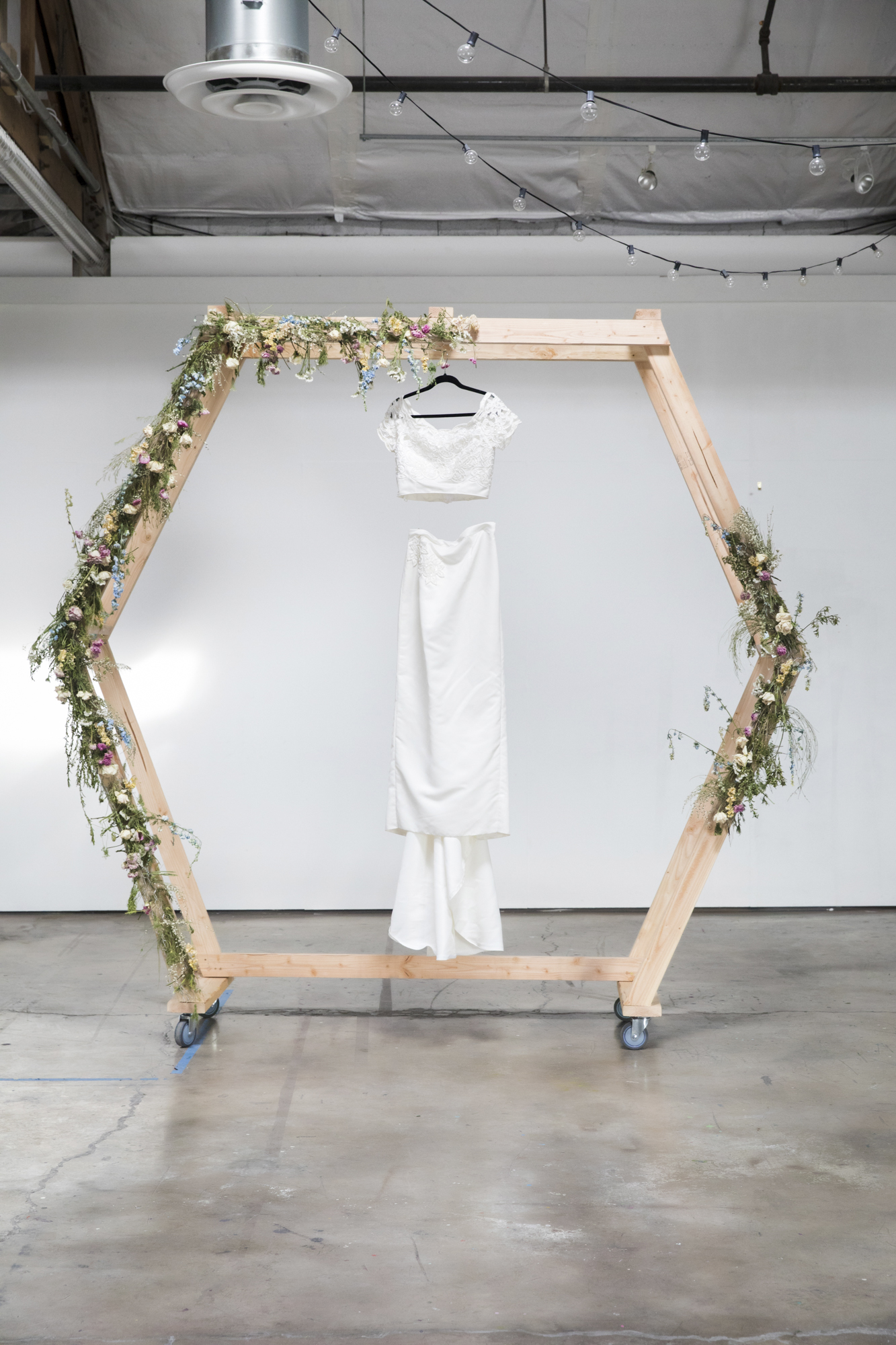 White eco-friendly wedding dress hanging on wooden stand