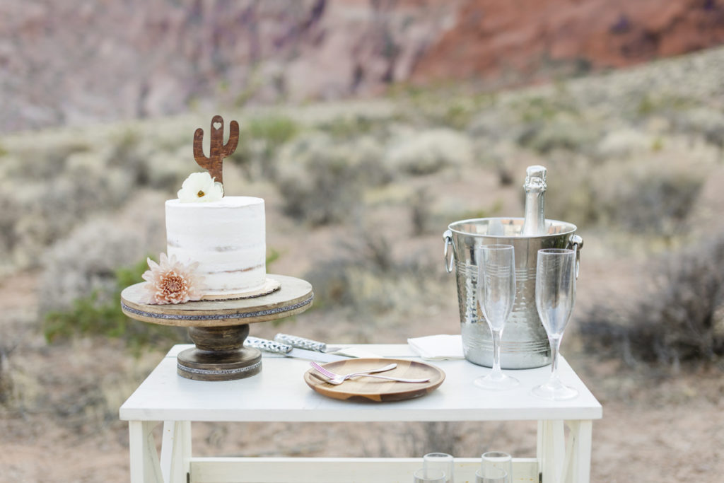 Wedding cake and champagne on wooden cart