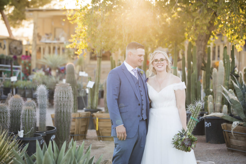 Bride and groom at sunset in front of numerous cacti