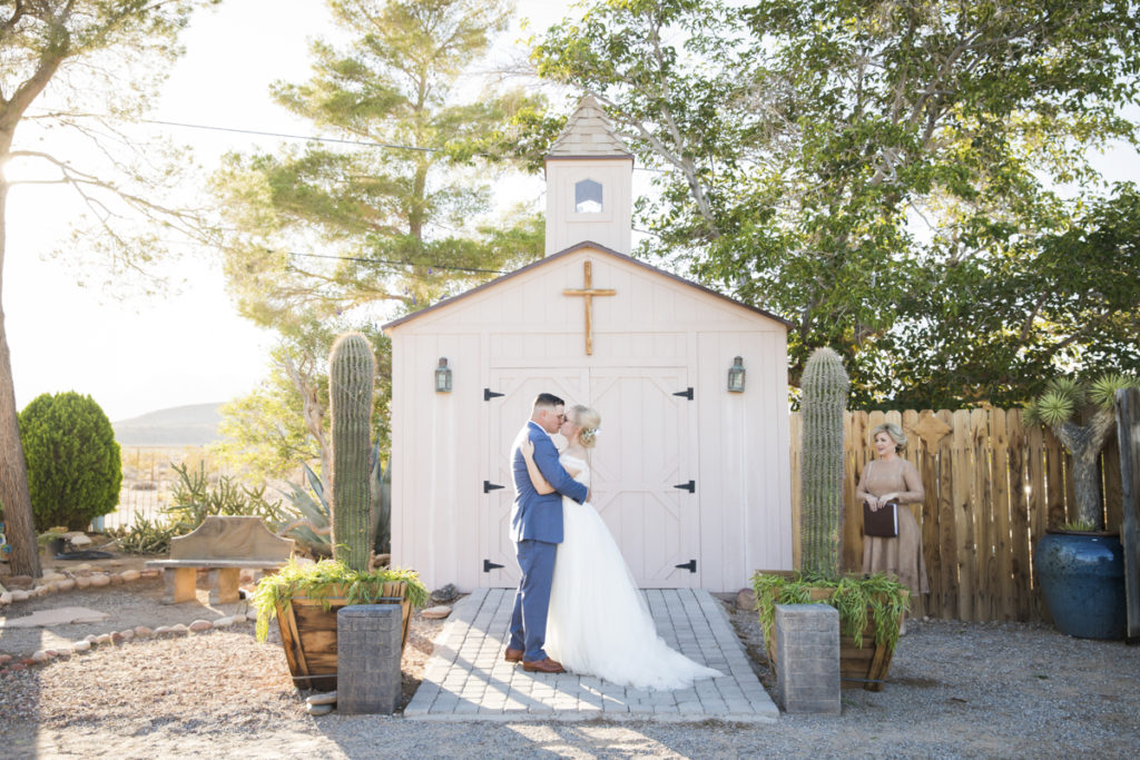 Newlywed couple kissing in front of outdoor chapel