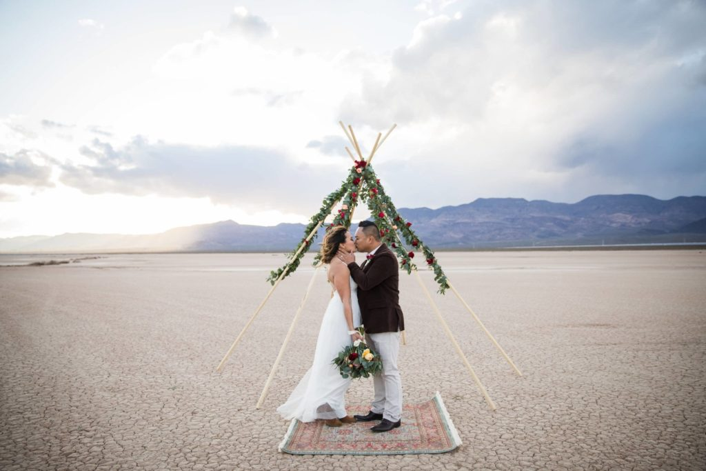 Couple has celebratory kiss in front of triangle arbor