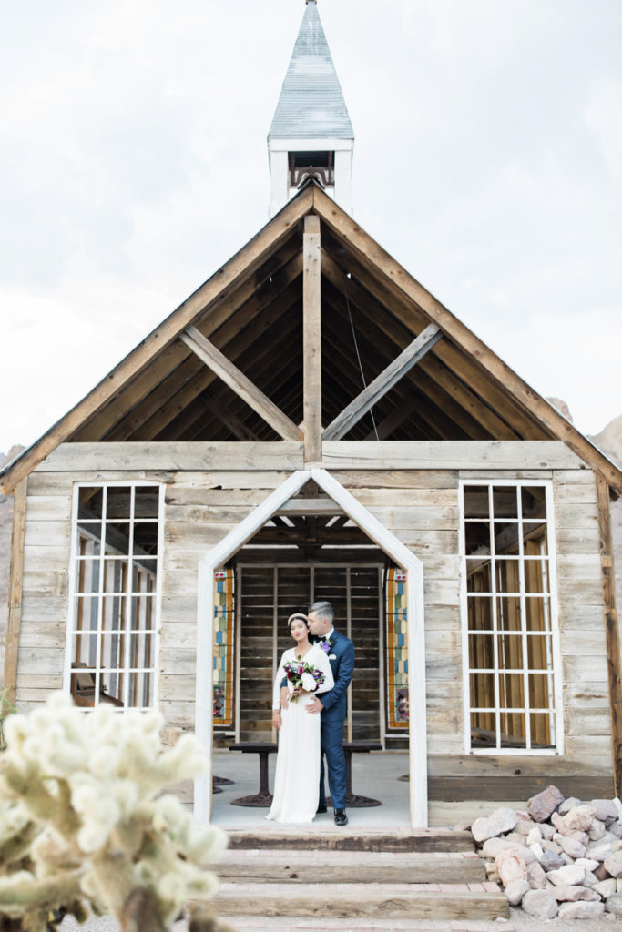 Newlywed couple embracing in front of outdoor chapel