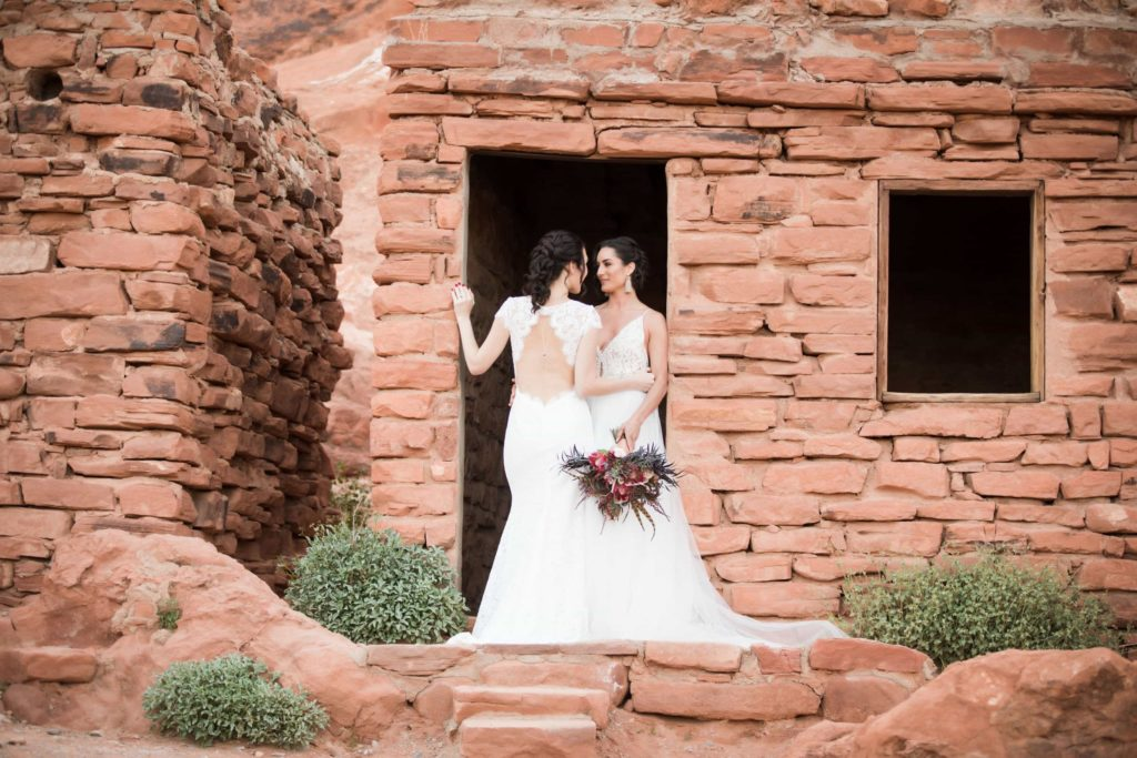 Same sex couple standing in white wedding dresses