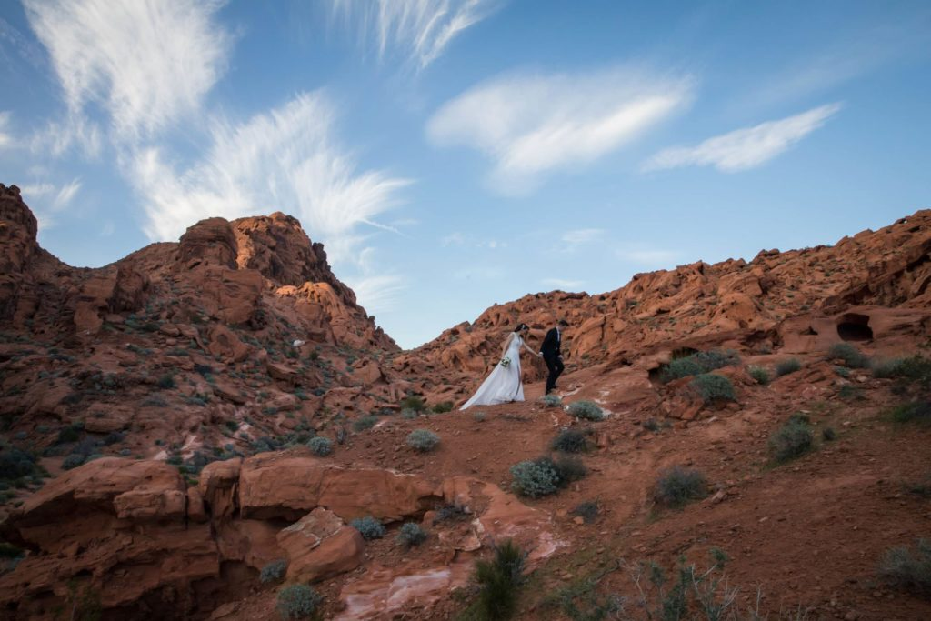 Couple far away walking up expansive mountain landscape