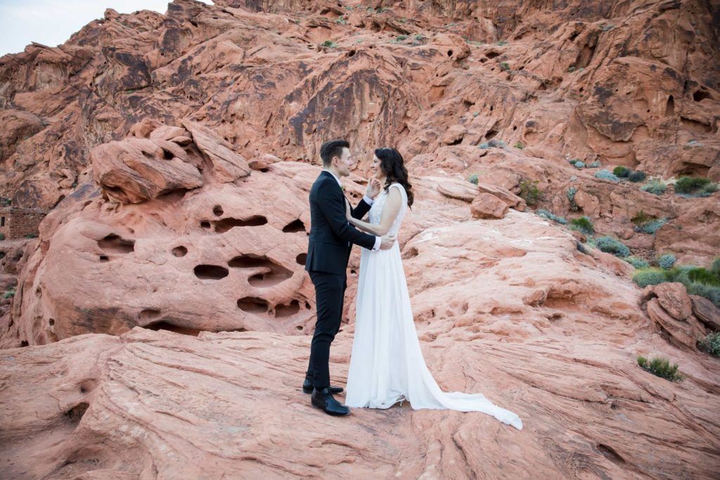 Couple standing face to face on mountain rock