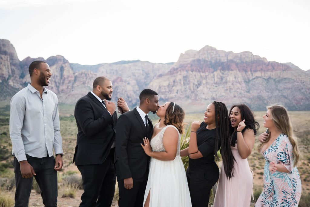 Wedding photo of family members watching happy couple kissing